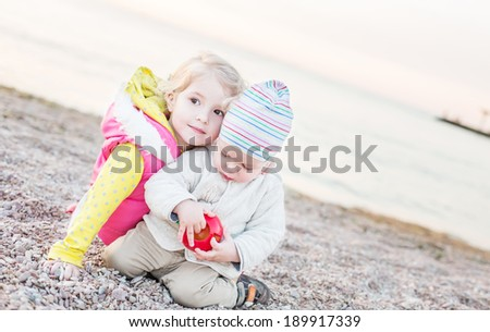 cute little brother and sister playing on the beach in spring time - stock photo