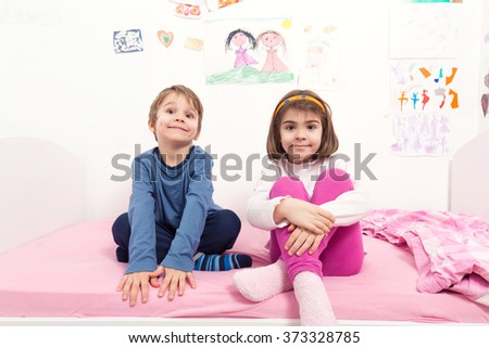 Cute little brother and sister sitting on the bed in their room and looking at camera - stock photo