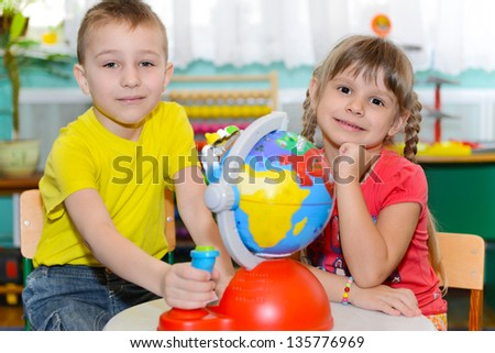 Cute little brother and sister study globe