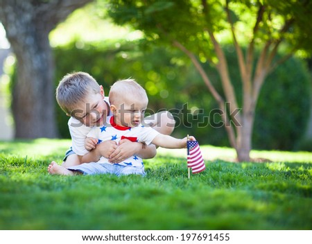 Cute little brothers sitting on a green lawn  - stock photo