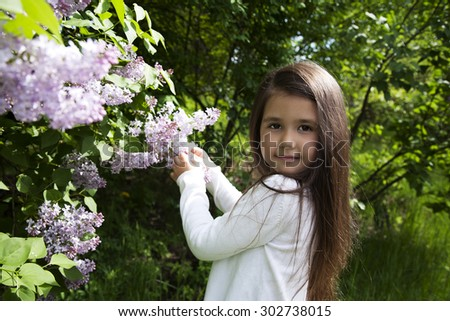 cute little brunette  girl, dressed in a white shirt , she holds a blossoming branch of lilac in her hands - stock photo