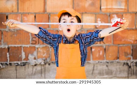 cute little builder  in hardhats with with measuring tape  working outdoors - stock photo