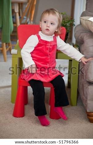 Cute little caucasian baby girl in red dress sitting on a red chair. - stock photo
