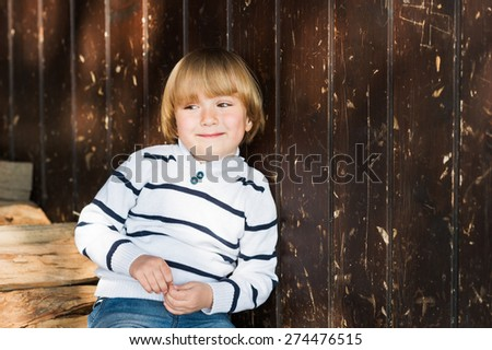 Cute little caucasian blond boy leaning on an old wooden wall, wearing white pullover - stock photo