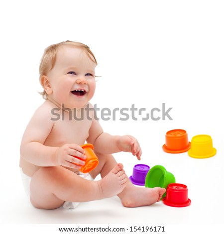 Cute little caucasian boy 11 months old sits and plays with toys on white background