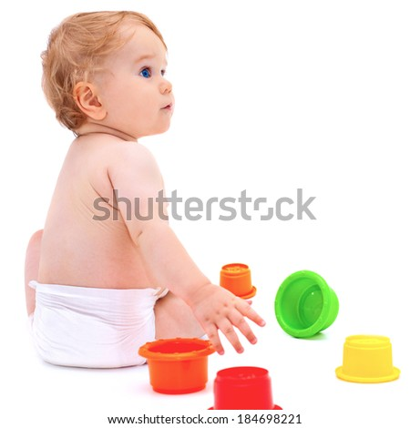 Cute little caucasian boy 11 months old sits and plays with toys on white background. A baby boy looks up - stock photo