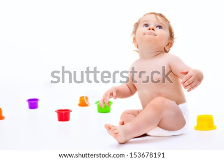 Cute little caucasian boy 11 months old sits surrounded with toys looks up on white background - stock photo