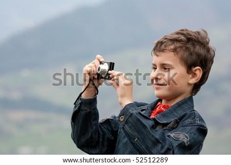 Cute little caucasian boy taking photos outdoor - stock photo