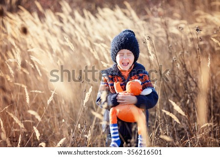 Cute little caucasian child, boy, holding fluffy toy, hugging it, in the park, on sunny winter day - stock photo