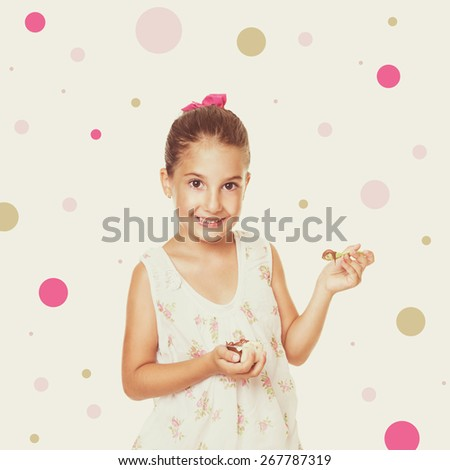 Cute little Caucasian girl in floral dress eating cocoa cream smiling looking at camera. Pastel filter and dots in the background, retouched, square format image. - stock photo