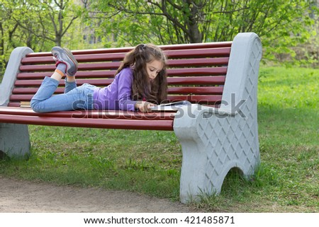 Cute little caucasian girl with beautiful long hair reading book lying on a bench in spring park - stock photo