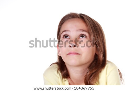 Cute little Caucasian girl with brown hair in a yellow outfit looking up  on an isolated white background with room for copy - stock photo