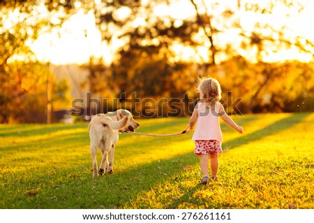 Cute little child, adorable girl with curly hair and her dog, yellow labrador walking away into the sunset light in a countryside park