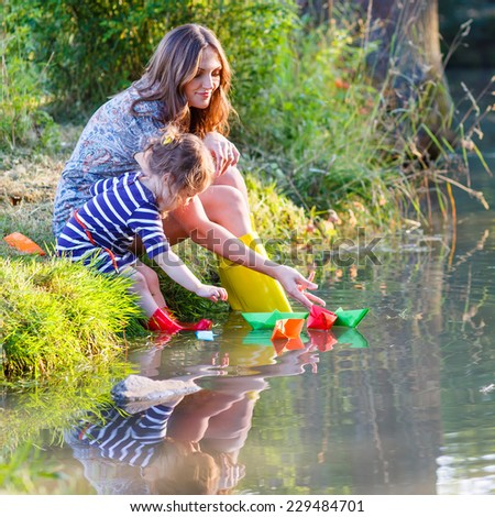 cute little child and young woman playing together with paper boats in a river. Creative leisure with kids. - stock photo