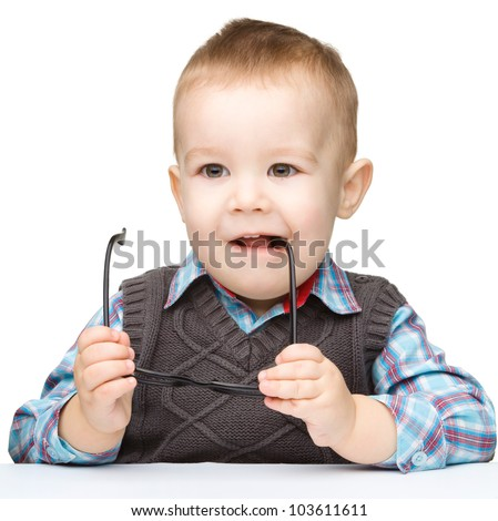 Cute little child biting glasses while sitting at table, isolated over white