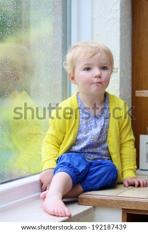 Cute little child, blonde curly toddler girl in colorful casual outfit sitting indoors on a rainy day looking through window with garden view - stock photo