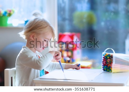 Cute little child, blonde preschooler girl is drawing and painting with colorful felt-tip pens at home or kindergarten sitting at small table in bright sunny playroom - stock photo
