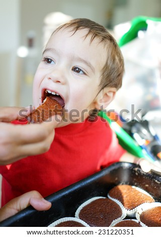 Cute little child eating cupcakes at home - stock photo