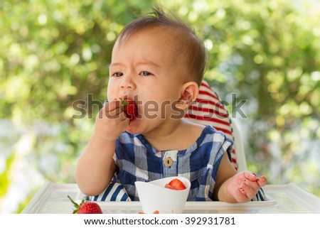Cute little child eating strawberries in garden