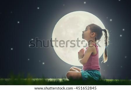 cute little child girl enjoying meditation and yoga on green grass on moon sky background - stock photo
