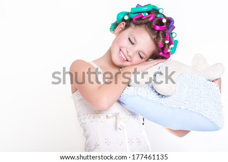 Cute little Child girl in pajamas sleeping on pillow in hair curlers, glamour child,bedtime. Funny little girl portrait. isolated on white background, studio. - stock photo