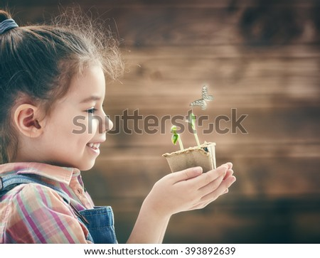 Cute little child girl planting seedlings. Fun little gardener. Spring concept, nature and care. - stock photo
