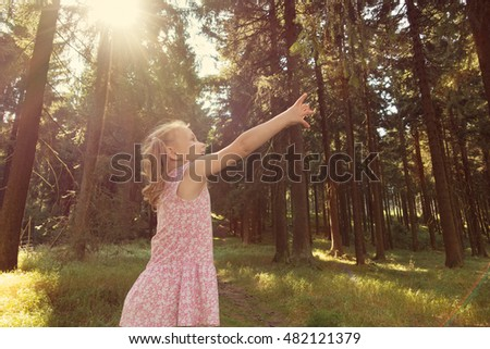 Cute little child girl reach branch in summer forest. Rays of the sunshine