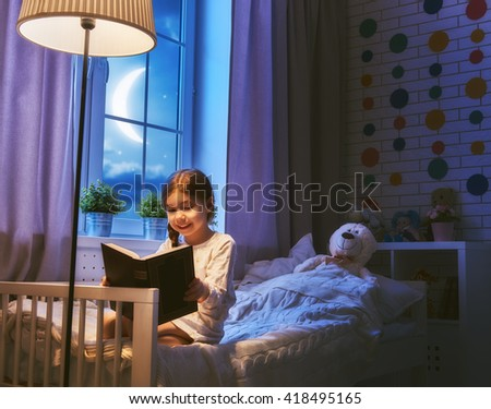 Cute little child girl reading a book under a lamp. Kid girl sitting in her bed on a dark moonlit night. - stock photo