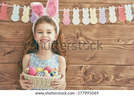 Cute little child girl wearing bunny ears on Easter day. Girl holding basket with painted eggs.