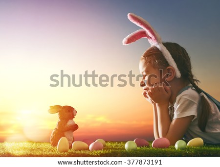 Cute little child girl wearing bunny ears on Easter day. Girl hunts for Easter eggs on the lawn. Girl with Easter eggs and bunny in the rays of the setting sun. - stock photo