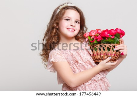 Cute little child girl with spring flowers, happy baby girl with basket of flowers. Isolated in studio on white background.  - stock photo