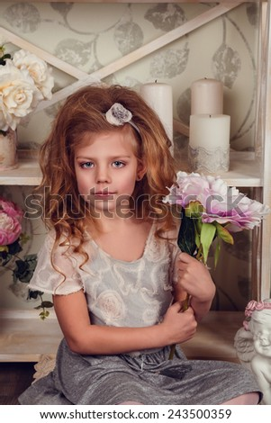Cute little child girl with spring flowers, happy baby girl with basket of flowers. retro phone, a rack with flowers and cute attributes