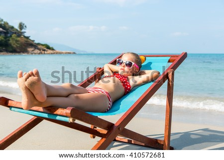 Cute little child in red swimsuit and white sunglasses enjoying on a sun lounger rest on the beach chair on tropical sandy beach sea shore. Sunbathing and leisure on sunny day.