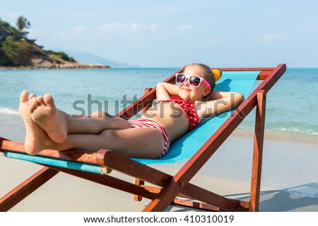 Cute little child in red swimsuit and white sunglasses smile and enjoying on a sun lounger rest on the beach chair on tropical sandy beach sea shore. Sunbathing and leisure on sunny day. - stock photo