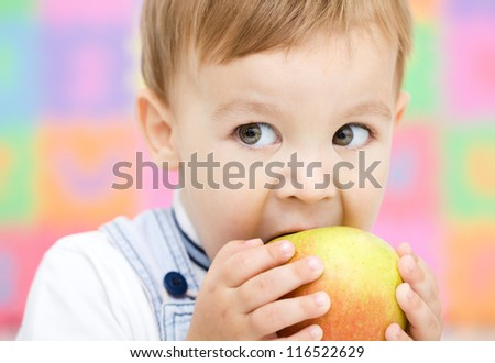 Cute little child is biting red apple and smile, isolated over white - stock photo