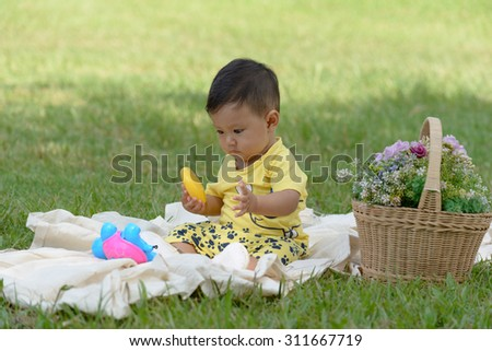 Cute little child is playing with toys while sitting on grass - stock photo