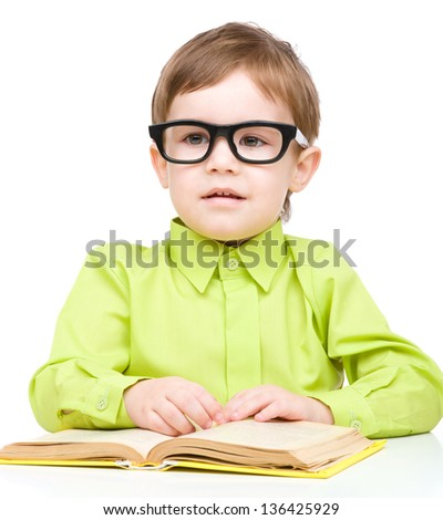 Cute little child play with book and wearing glasses while sitting at table, isolated over white - stock photo