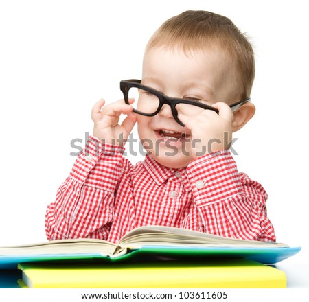 Cute little child play with book while sitting at table and wearing glasses, isolated over white
