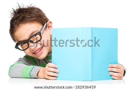 Cute little child plays with book and wearing glasses while sitting at table, isolated over white - stock photo