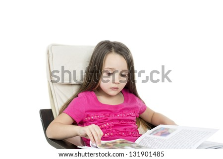 cute little child sitting in chair at home and reading book with copy space for your text
