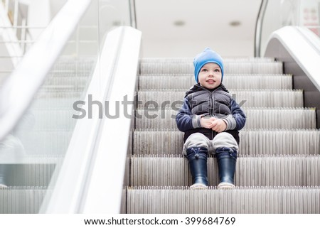 Cute little child sitting on moving staircase in shop - stock photo