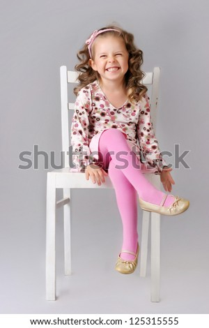 Cute little child sitting on the chair and smiling. wearing pink clothes - stock photo