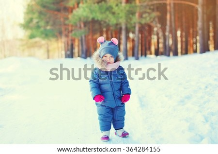 Cute little child walking on snow in winter forest