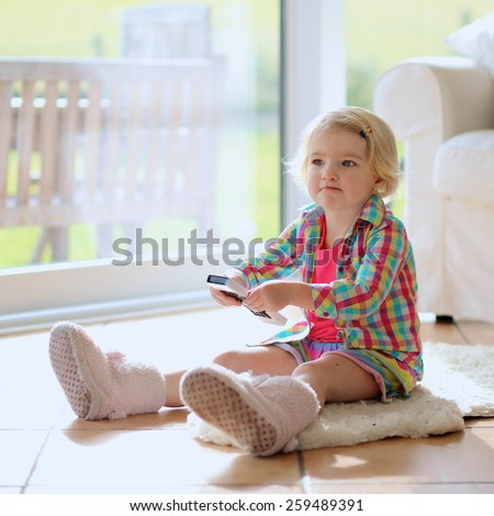 Cute little child, 3 years old preschooler girl watching tv at home sitting comfortable on the tiles floor - stock photo