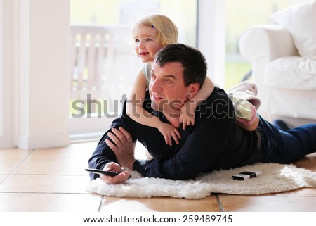 Cute little child, 3 years old preschooler girl watching tv lying together with her father comfortable on the tiles floor - casual lifestyle, happy family at home - stock photo