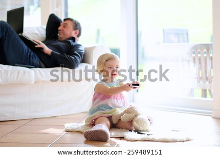 Cute little child, 3 years old preschooler girl watching tv sitting on the tiles floor, her father lying comfortable with laptop on sofa - happy family at home - stock photo