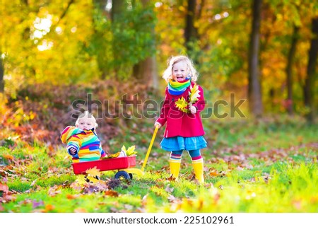 Cute little children, adorable toddler girl and a funny baby boy, brother and sister, playing in a sunny autumn park with a wheel barrow and colorful leaves