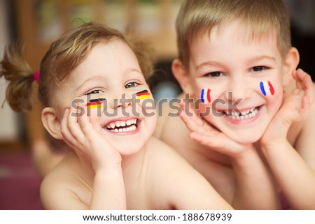 Cute little children couple having fun with European flags on cheeks - stock photo