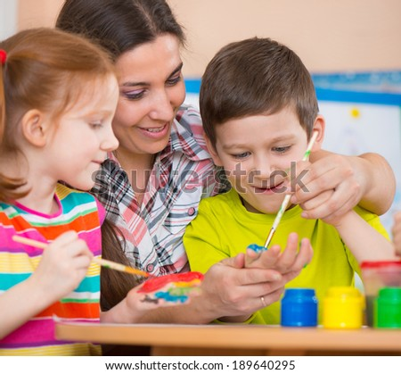 Cute little children drawing with teacher at preschool class - stock photo