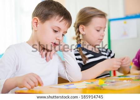 Cute little children having applique lesson at kindergarten - stock photo